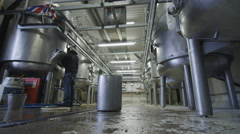4K Worker in a brewery cleaning out tanks with a water hose Stock Footage