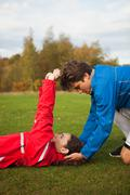 Personal trainer assisting young woman with warm up exercises Stock Photos