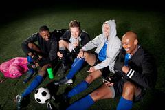 Soccer team resting on pitch after game - stock photo