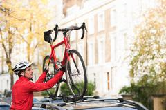 Mid adult man lifting bicycle onto car roof rack - stock photo