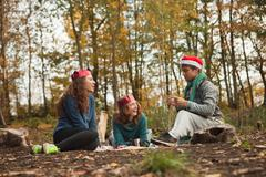 Young friends in forest wearing Santa hats and crowns Stock Photos
