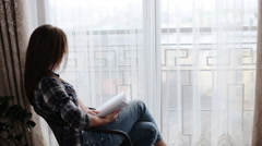 Cute woman wearing blue jeans and grey t-shirt sitting on the table in front of Stock Footage