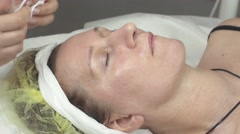 Cosmetologist put cotton pad, cheesecloth on adult woman face in beauty saloon Stock Footage