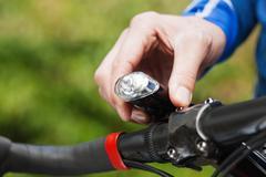 Man adjusting bicycle light, close up - stock photo
