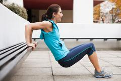 Woman in sportswear performing tricep dips - stock photo
