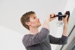 Man installing light fixture in house Stock Photos