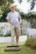 Older man mowing lawn in backyard Stock Photos