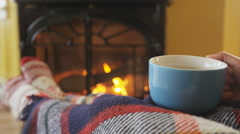 Stock Video Footage of Woman Drinking Coffee Cup by Fireplace In Winter Cozy With Blanket Cover