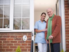 Portrait of nurse and senior man at front door of home Stock Photos