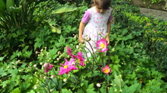 Slow motion little girl smelling flower in the garden Stock Footage