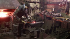 Blacksmith working on metal on anvil at forge Stock Footage
