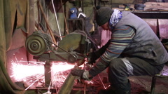Craftsman sawing metal with disk grinder in workshop Stock Footage