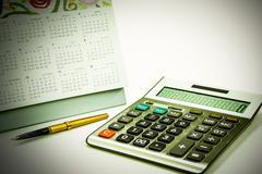 Calculator fountain pen and calendar on white background - stock photo