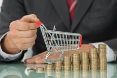 Close-up Of Businessman Hand Holding Small Shopping Cart Placed Near Stack Of - stock photo