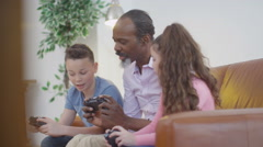 4K Happy grandfather trying to learn to play video games with grandchildren Stock Footage