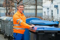 Happy Working Man Standing Near Dustbin On Street - stock photo