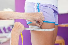 Trainer measuring girls leg in gym Stock Photos