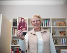 Portrait of senior woman holding photograph of younger self Stock Photos