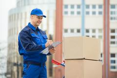 Portrait Of Confident Delivery Man With Parcels And Clipboard Against Truck Stock Photos