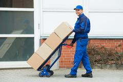 Mature Happy Delivery Man Carrying Boxes On A Hand Truck On Street - stock photo