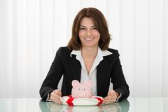 Happy Young Businesswoman Sheltering Piggybank With Lifebelt - stock photo