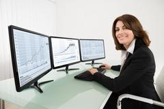 Happy Female Stock Market Broker Working On Multiple Computers In Office - stock photo