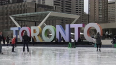 Ice skaters at Nathan Phillip's Square with big Toronto sign in the background Stock Footage