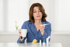 Sick Woman Looking At Thermometer While Holding Cup Of Tea Stock Photos