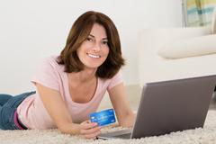 Excited Woman Lying On Carpet Shopping Online On Laptop With Debit Card Stock Photos
