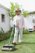 Older woman mowing lawn in backyard Stock Photos