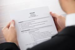 Close-up Of Businessman Holding Resume In Office - stock photo