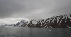 Snowy Mountains stretch into cloudy distance next to arctic bay Stock Footage