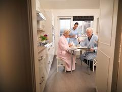 Nurse assisting senior couple with breakfast in kitchen Stock Photos