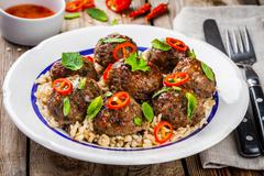 homemade meatballs with wild rice, mint, green onions and chili sauce - stock photo