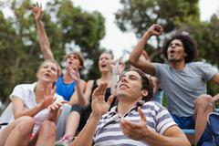 Friends cheering at sporting event - stock photo