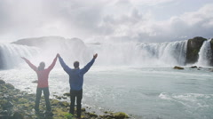 Cheerful Couple Raising Hands At Godafoss Waterfall - Happy Success Hiking Stock Footage