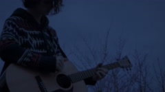 Handsome man with long hair playing acoustic guitar and singing at night time - stock footage