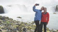 Couple Photographing Against Godafoss Waterfall Using Smart Phone Stock Footage