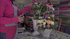 Florist preparing bouquet in gift shop - stock footage
