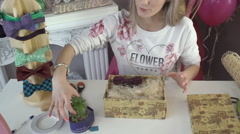 Girl puts a flower in a gift composition Stock Footage