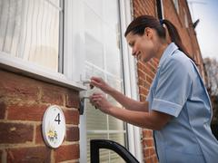 Nurse unlocking front door of patients house Stock Photos