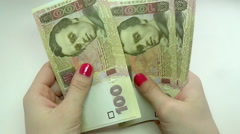 Close-up of a businessman's hands counting hundred  hryvnia bills at a table Stock Footage