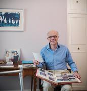 Portrait of senior man holding photograph album - stock photo