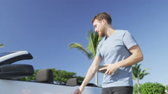 Man Holding Smartphone Getting In Convertible Car - Young Urban Professional Stock Footage