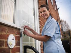 Portrait of nurse unlocking front door of patients house Stock Photos