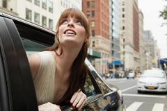 Young woman leaning out of taxicab window, looking up - stock photo