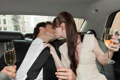 Newlywed couple kissing in car with champagne Stock Photos