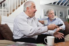 Senior men looking at television in disbelief Stock Photos