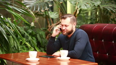 Handsome bearded businessman talking on the phone cheerfully during his coffee Stock Footage