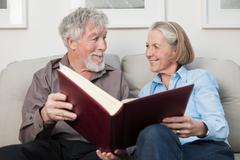 Senior couple with photograph album - stock photo